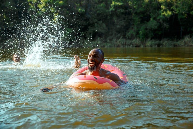 Счастливый человек имея потеху, laughting и плавая в реке стоковые фото