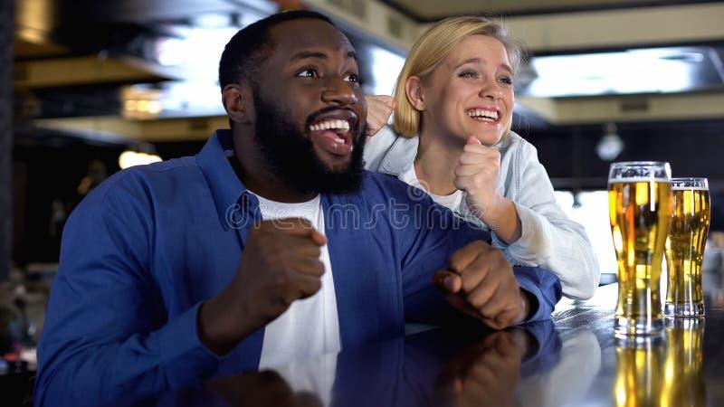 Счастливый человек и женщина наблюдая, как онлайн спичка поддержала любимую команду, цель стоковое изображение
