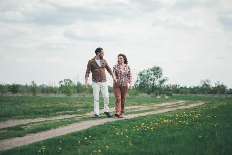 Счастливый человек и женщина наслаждаясь романтичной прогулкой на луге цветка стоковое изображение