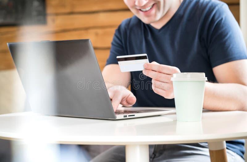 Счастливый человек оплачивая с кредитной карточкой или используя онлайн банк стоковое фото