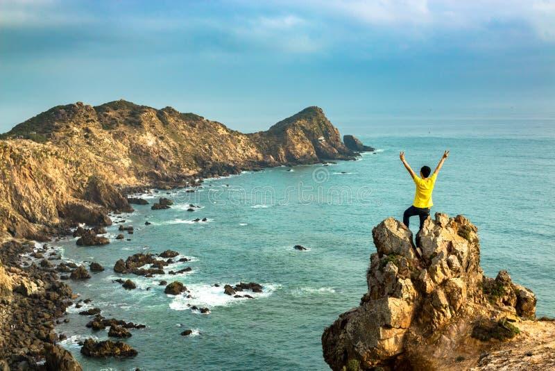 Счастливый человек празднуя победу на верхней части горы океаном стоковое изображение