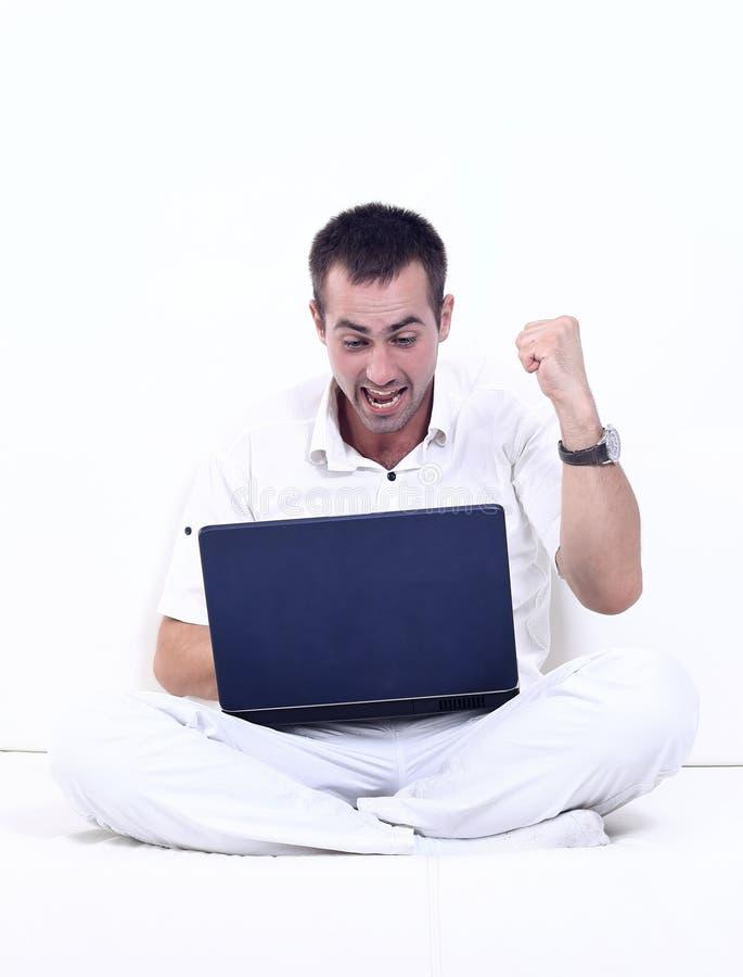 Счастливый человек работая на компьтер-книжке, сидя на кресле стоковое фото