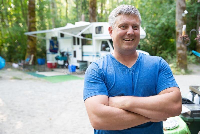 Счастливый человек располагаясь лагерем снаружи с RV стоковые изображения