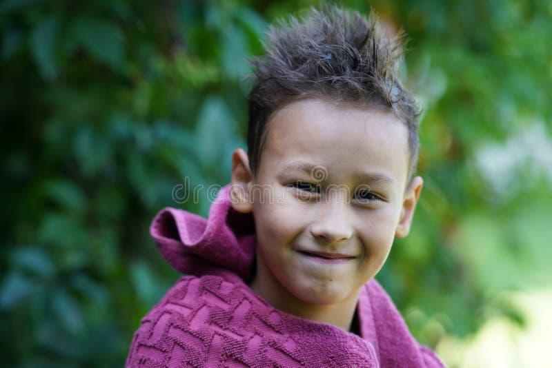 Счастливый outdoors мальчика на листьях лета зеленых стоковое фото