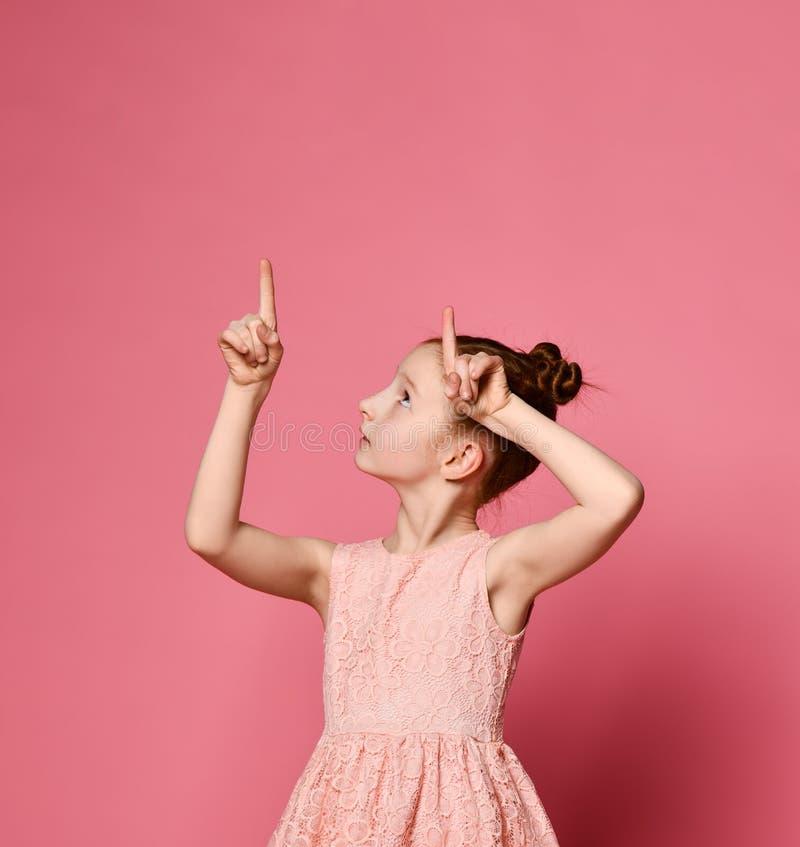 Счастливый redhead девушки в розовом платье представляя с рукой на бедре пока имеющ идею и смотрящ камеру стоковые изображения