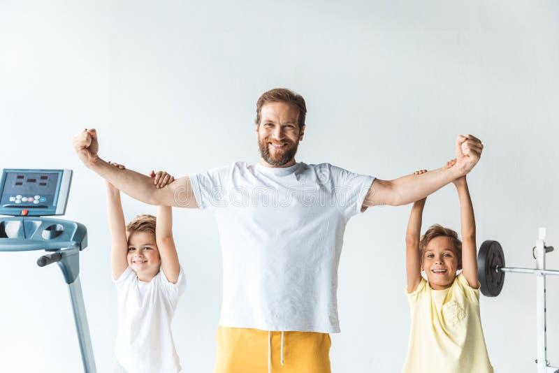 счастливый sportive отец и сыновья усмехаясь на камере стоковое фото