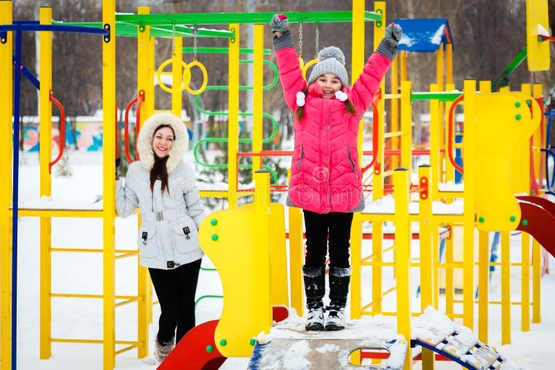 2 счастливых девушки, мать и дочь играя на спортивной площадке a стоковые фото