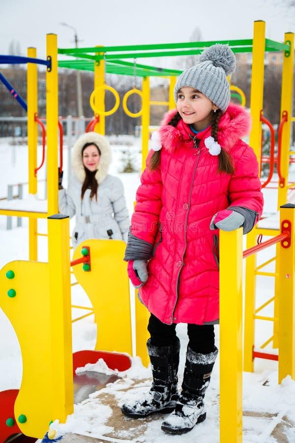 2 счастливых девушки, мать и дочь играя на спортивной площадке стоковая фотография