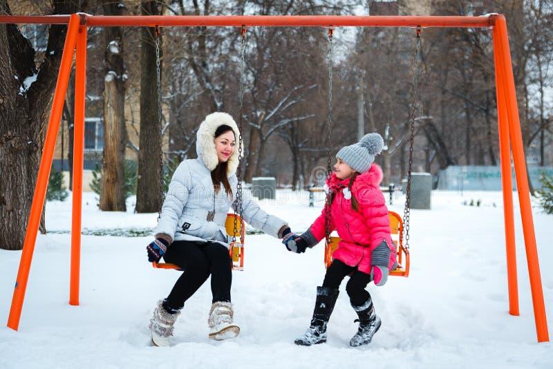 2 счастливых девушки, мать и дочь сидя на качании на pl стоковые фотографии rf