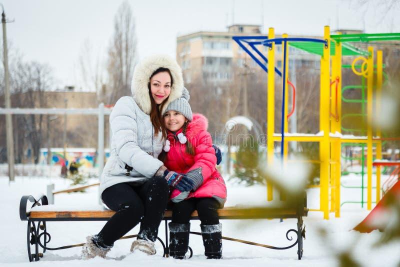 2 счастливых девушки, мать и дочь сидя на стенде на pl стоковая фотография