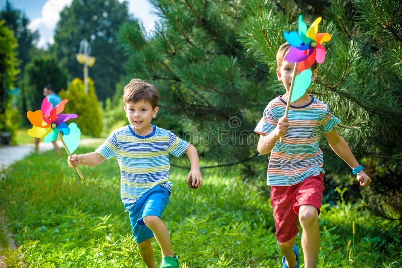 2 счастливых дет играя в саде с pinwheel ветрянки Прелестные братья отпрыска лучшие други Милая весна улыбки мальчика ребенк стоковые изображения