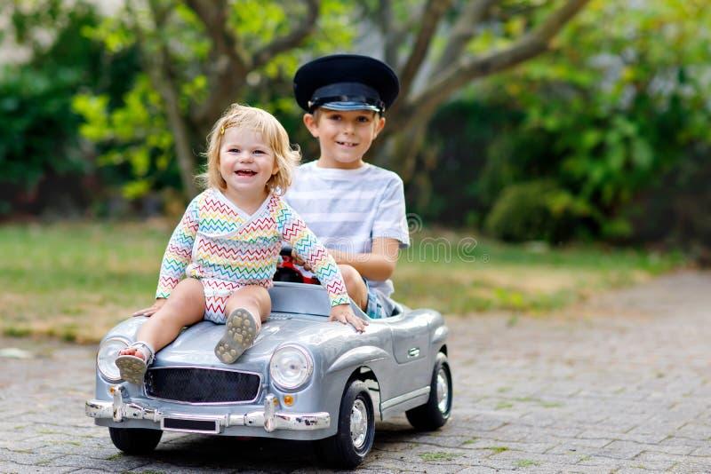 2 счастливых дет играя с большим старым автомобилем игрушки в лете садовничают, outdoors Оягнитесь мальчик управляя автомобилем с стоковое изображение rf