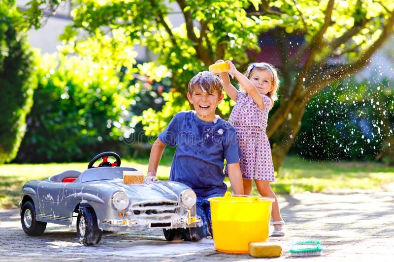 2 счастливых дет моя большой старый автомобиль игрушки в саде лета, outdoors Мальчик брата и девушка малыша маленькой сестры стоковая фотография