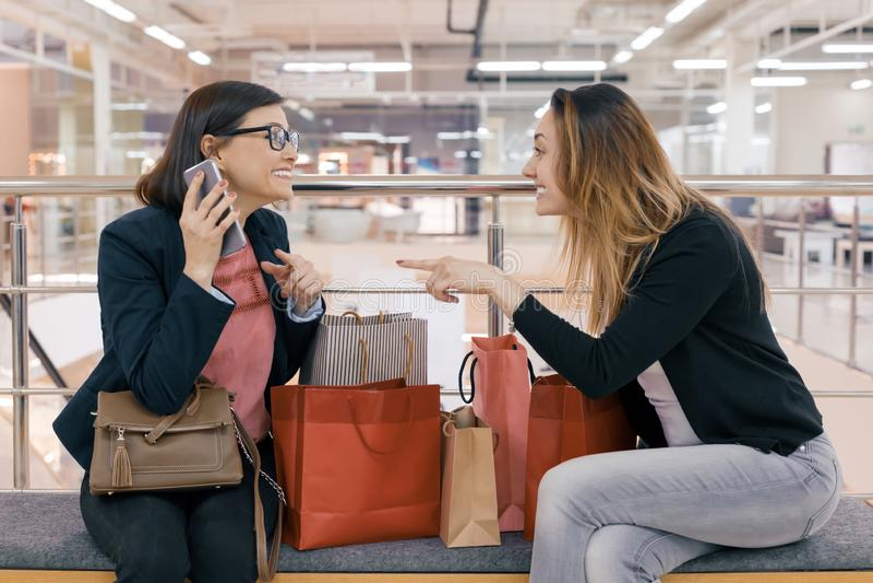 2 счастливых друз с хозяйственными сумками, женщины взрослых женщин говоря усаживание в торговом центре, с много приобретений стоковая фотография rf