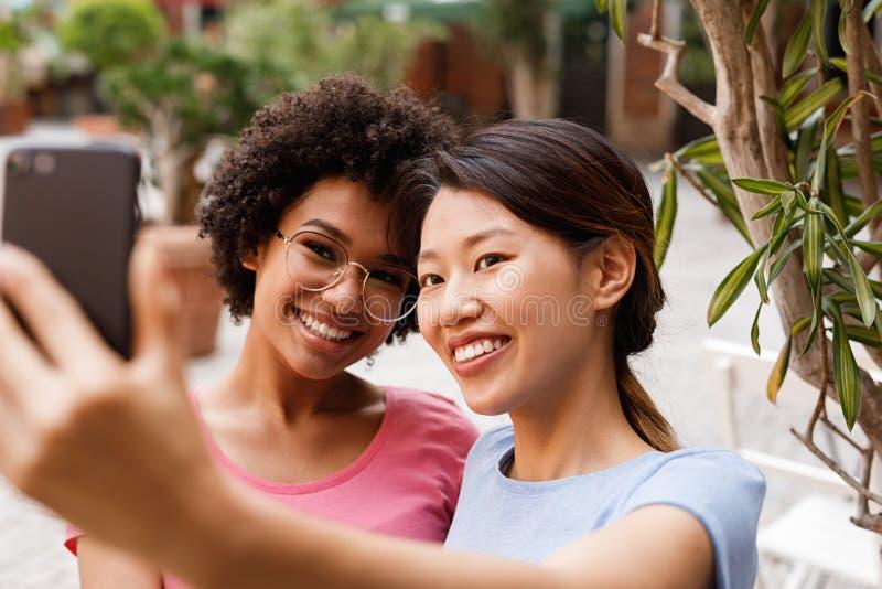 2 счастливых женщины принимая selfie стоковые фотографии rf