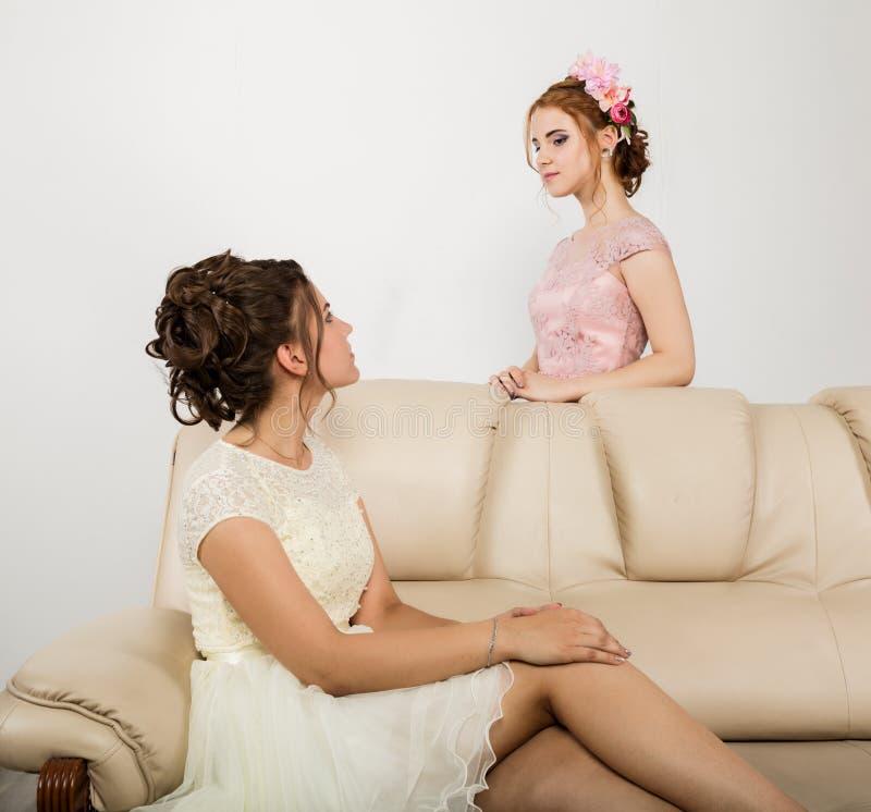 2 счастливых красивых молодой женщины в элегантных платьях, нежной истории стоковая фотография rf