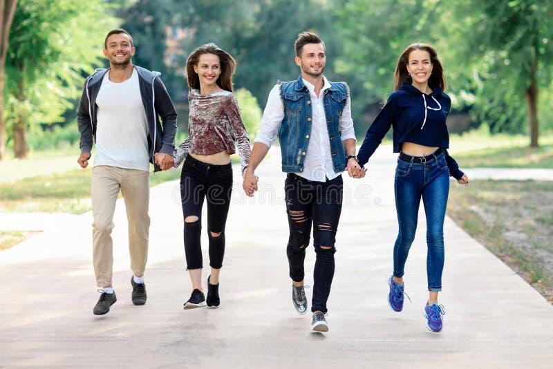 2 счастливых люди и женщины бежать держащ руки в парке стоковая фотография