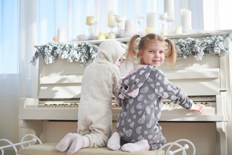 2 счастливых маленькой девочки в пижамах играют рояль на Рождество стоковое фото rf