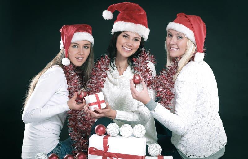 3 счастливых маленькой девочки одетой как Санта Клаус сидя с бушелем стоковая фотография rf