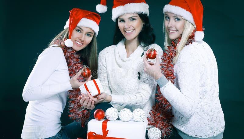 3 счастливых маленькой девочки одетой как Санта Клаус сидя с b стоковые изображения rf