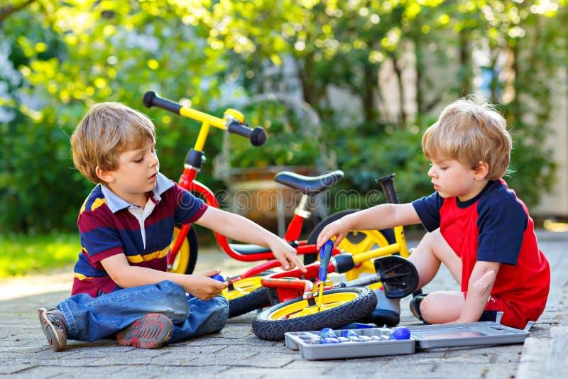2 счастливых мальчика маленького ребенка ремонтируют цепь на велосипедах и колесе изменения велосипеда баланса стоковое фото