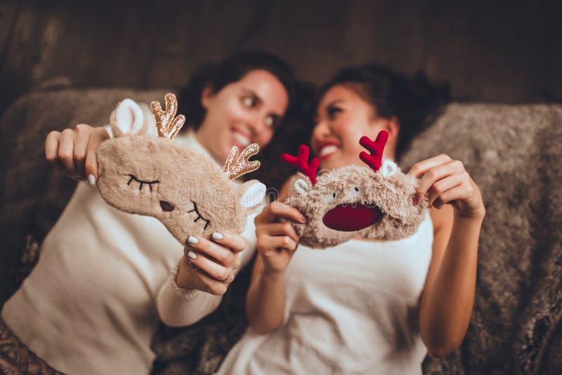 2 счастливых подруги лежат в кровати и нося маске спать дома около рождественской елки в уютном интерьере стоковая фотография rf