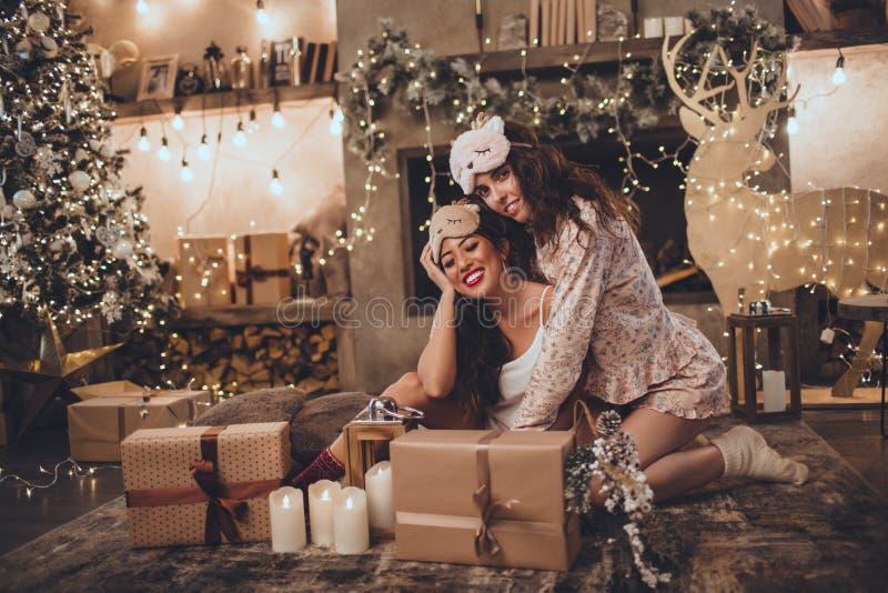 2 счастливых подруги носят маску спать дома около рождественской елки в уютном интерьере Интерьер с рождеством стоковая фотография rf
