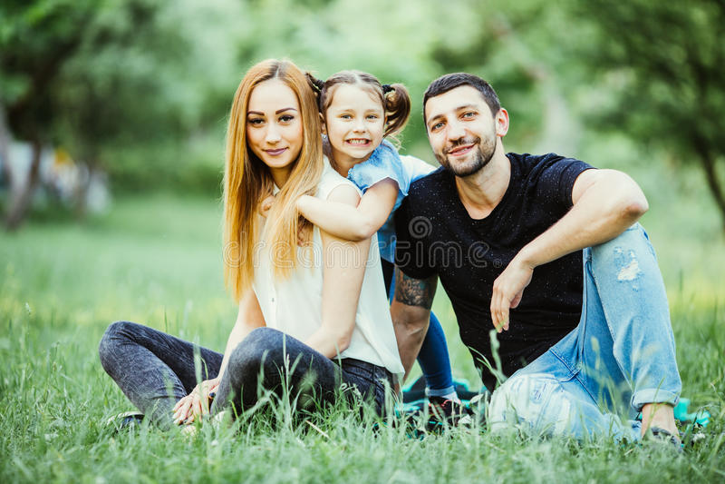 Счастье и сработанность в семейной жизни семья принципиальной схемы счастливая Молодые мать и отец с их дочерью в парке семья сча стоковая фотография