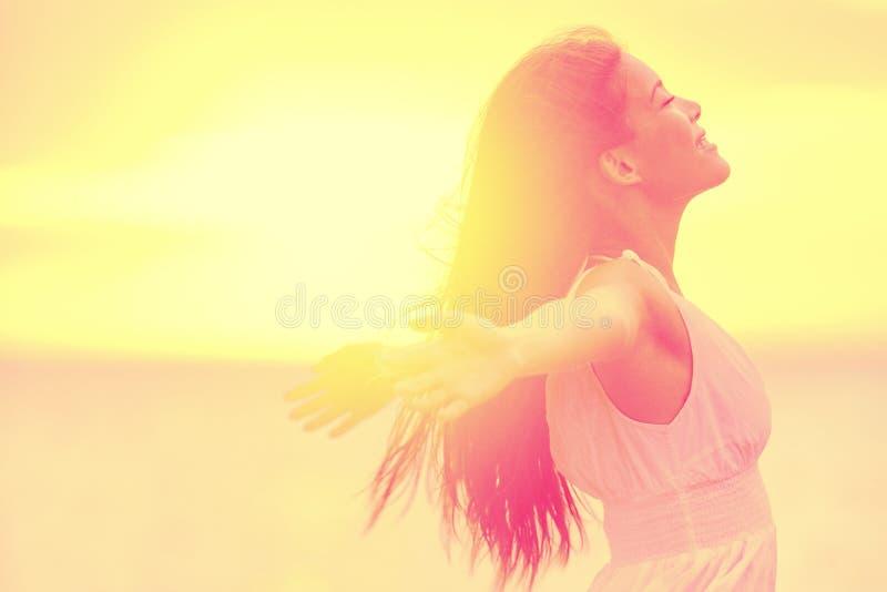 Счастье - свободная счастливая женщина наслаждаясь заходом солнца стоковое изображение