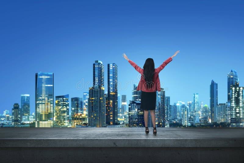 Счастливая азиатская бизнес-леди стоя на крае крыша стоковая фотография