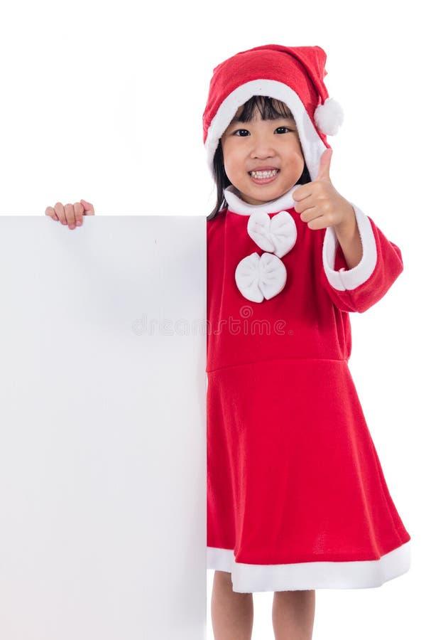 Счастливая азиатская китайская маленькая девушка santa держа пустую доску стоковые фотографии rf