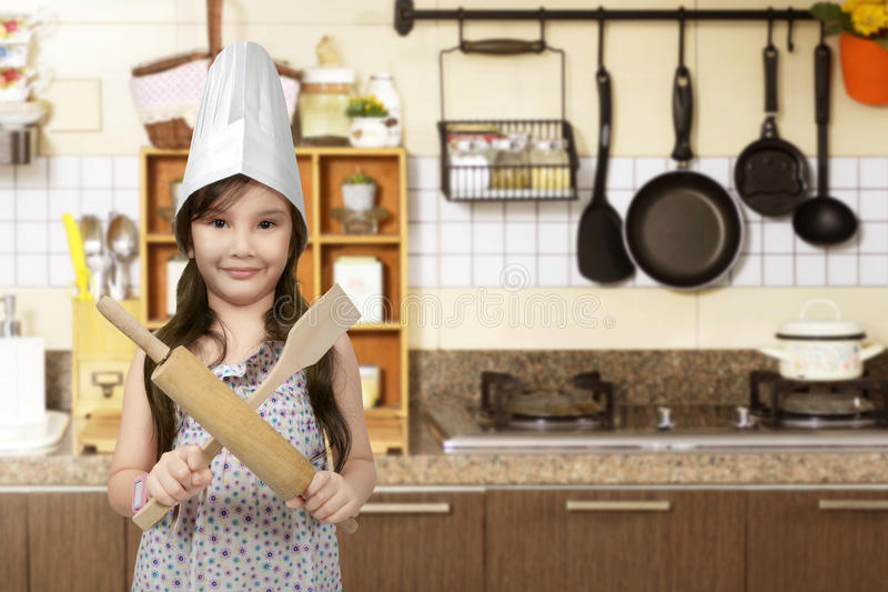 Счастливая азиатская маленькая девочка при шляпа шеф-повара держа варя прибор стоковые фото