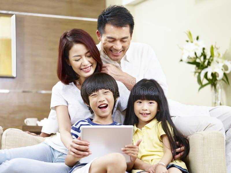 Счастливая азиатская семья используя цифровую таблетку совместно стоковое фото rf