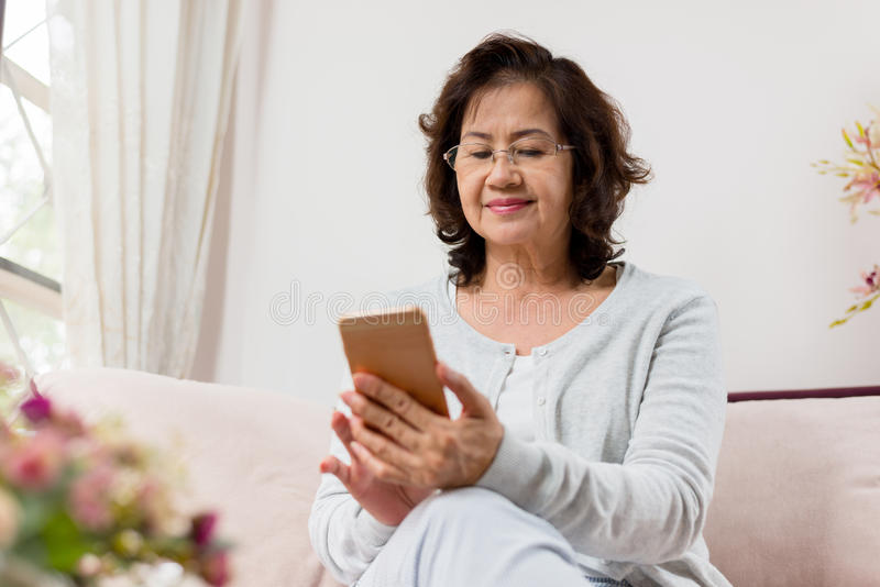 Счастливая азиатская старшая женщина сидя на софе и используя умный телефон стоковое изображение rf