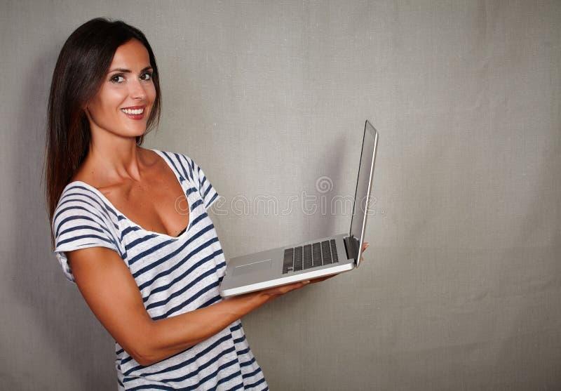 Счастливая дама брюнет держа беспроволочную компьтер-книжку стоковая фотография