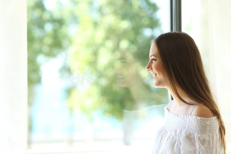 Счастливая дама смотря через окно стоковое фото rf