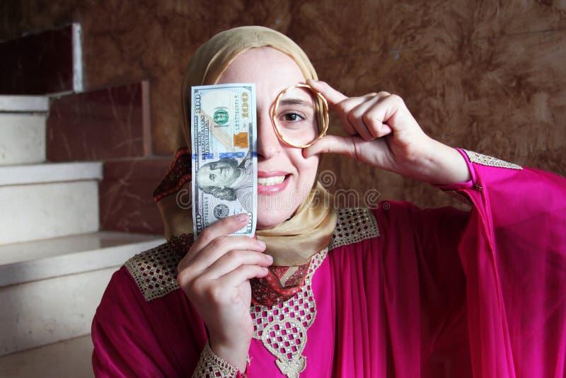 Счастливая арабская мусульманская женщина с золотом и деньгами стоковая фотография rf