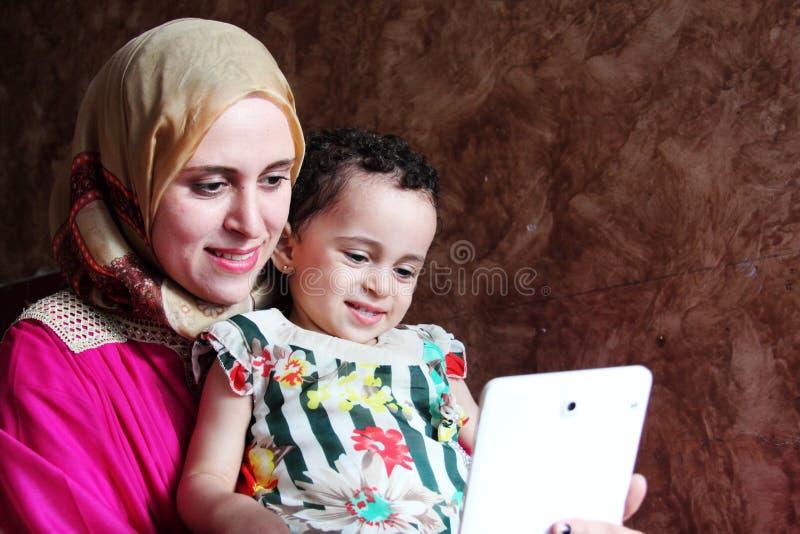 Счастливая арабская мусульманская мать при ее ребёнок принимая selfie стоковая фотография