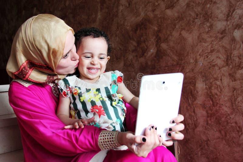 Счастливая арабская мусульманская мать при ее ребёнок принимая selfie стоковые фотографии rf