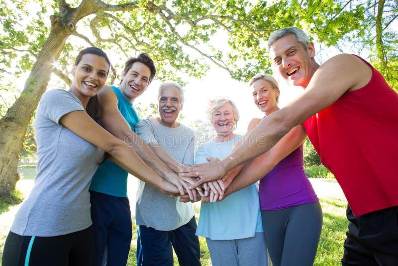 Счастливая атлетическая группа кладя их руки совместно стоковые фото