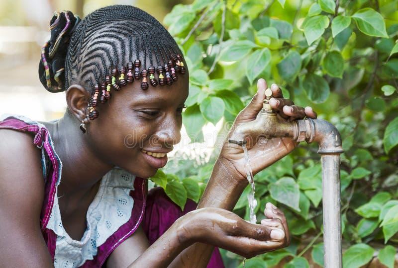 Счастливая африканская школьница наслаждаясь чистой водой от крана в Bama стоковая фотография
