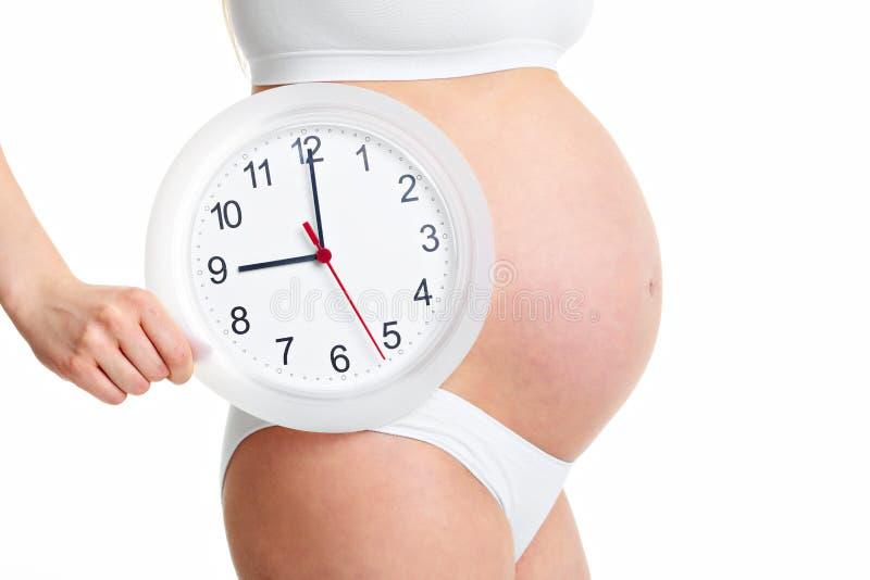 Счастливая беременная женщина держа часы стоковые фото