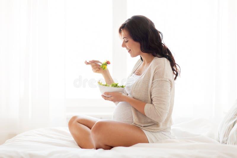 Счастливая беременная женщина есть салат дома стоковое фото rf