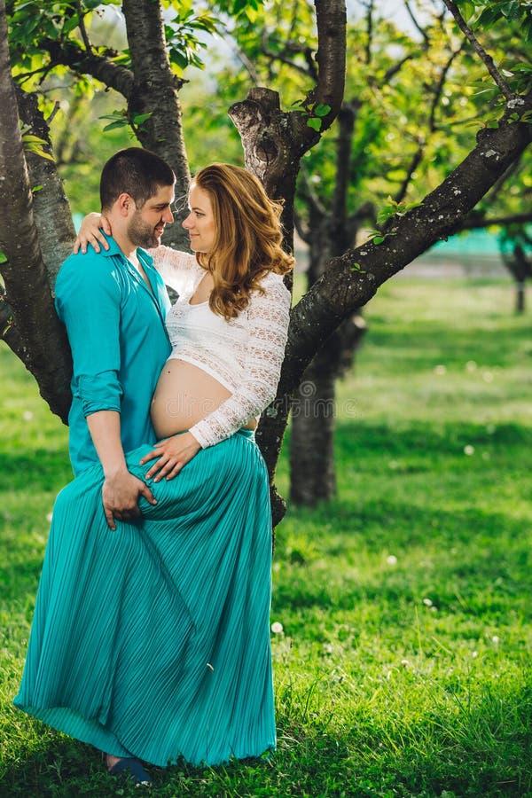 Счастливая беременная женщина и ее супруг в древесине на заходе солнца весны стоковое изображение