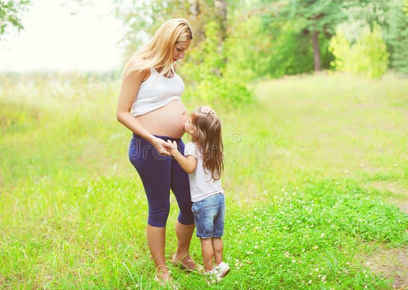 Счастливая беременная женщина, дочь маленького ребенка целуя мать tummy стоковое изображение rf