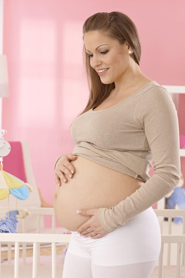 Счастливая беременная женщина с нагим животом стоковое фото