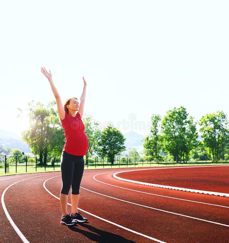 Счастливая беременная женщина с поднятыми руками на стадионе спорта стоковые изображения