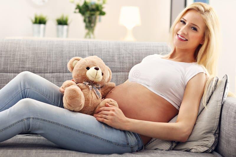Счастливая беременная женщина с плюшевым медвежонком стоковая фотография rf