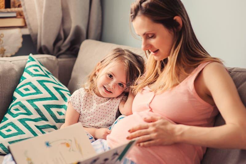 Счастливая беременная книга чтения матери к ее дочери младенца дома стоковое изображение