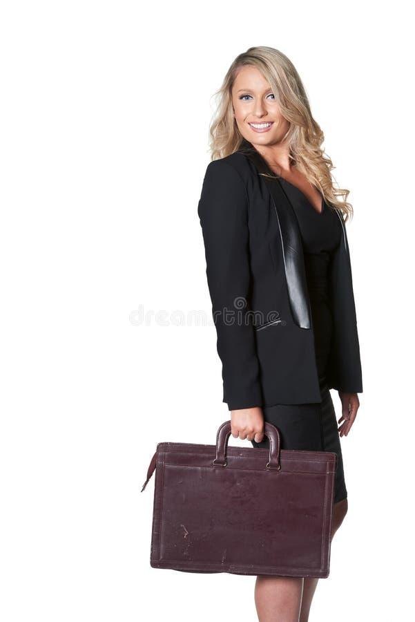 Счастливая белокурая бизнес-леди в темном костюме при изолированный портфель, стоковая фотография